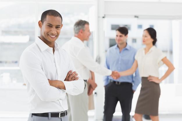 Giovane uomo d'affari con squadra dietro di lui sorridendo alla telecamera