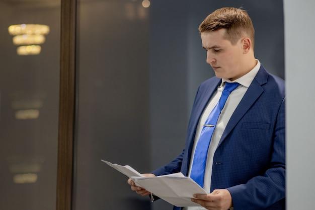 Documenti di lavoro del giovane imprenditore guardando attraverso i documenti nella cartella, seduto alla scrivania in ufficio.