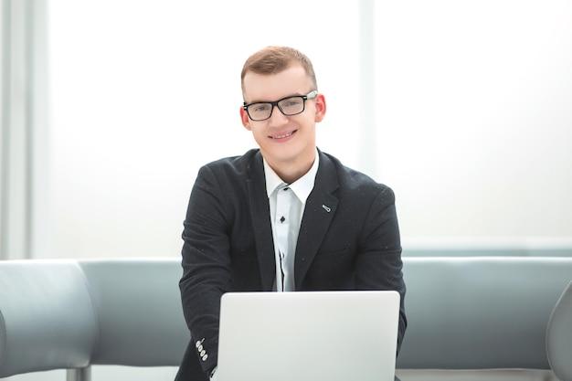Giovane uomo d'affari che lavora su un computer portatile in un ufficio luminoso