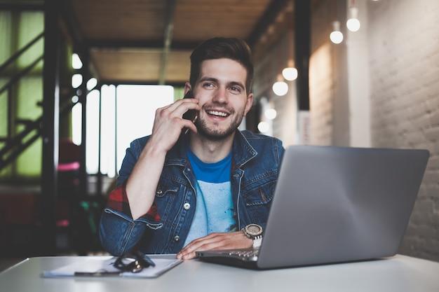 Giovane imprenditore lavora in ufficio, seduto alla scrivania, guardando lo schermo del computer portatile, sorridendo.