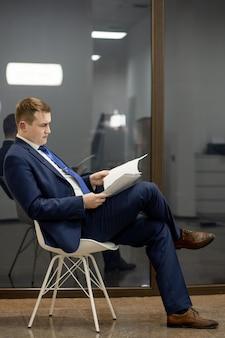 Giovane uomo d'affari che lavora con i documenti guardando attraverso i documenti nella cartella, seduto alla scrivania in ufficio.