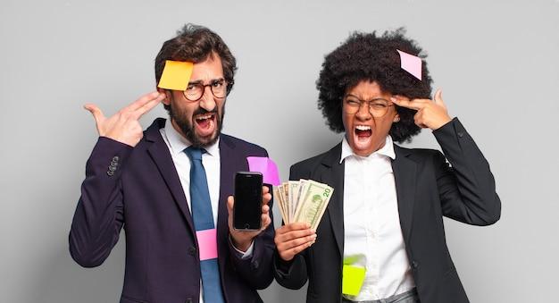 Giovani imprenditori che sembrano infelici e stressati, gesto di suicidio che fa il segno della pistola con la mano, indicando la testa. concetto di business umoristico