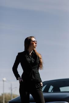 Giovane imprenditrice in abbigliamento nero con una macchina costosa