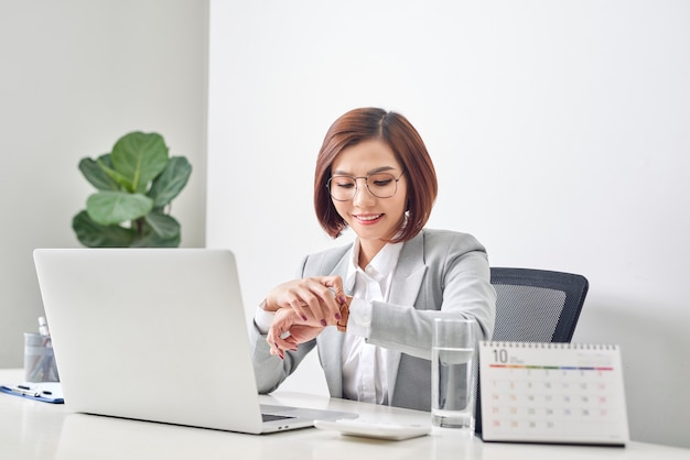Giovane imprenditrice controllando il tempo sul suo orologio da polso sul posto di lavoro. gestione del tempo