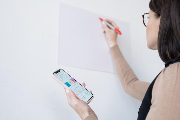 Giovane imprenditrice o allenatore in possesso di smartphone con diagramma di flusso mentre va a riscriverlo sulla lavagna al seminario