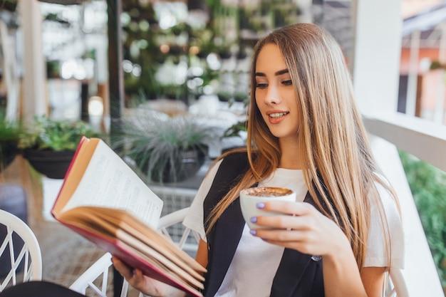 Giovane donna di affari che beve latte nella caffetteria
