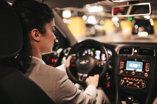 Giovane imprenditrice alla guida della sua auto nel garage sotterraneo pubblico.