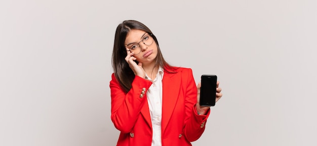 Giovane donna d'affari che si sente annoiata, frustrata e assonnata dopo un compito noioso, noioso e noioso, tenendo il viso con la mano