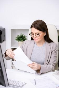 Giovane imprenditrice in bicchieri seduti a tavola e mettere il documento in busta durante l'invio di lettera commerciale