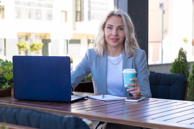 Giovane imprenditrice in abito grigio si siede a un tavolo in un bar e scrive note vedere il webinar.