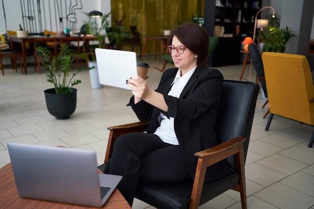 Giovane imprenditrice con videochiamata con tablet durante la pausa caffè