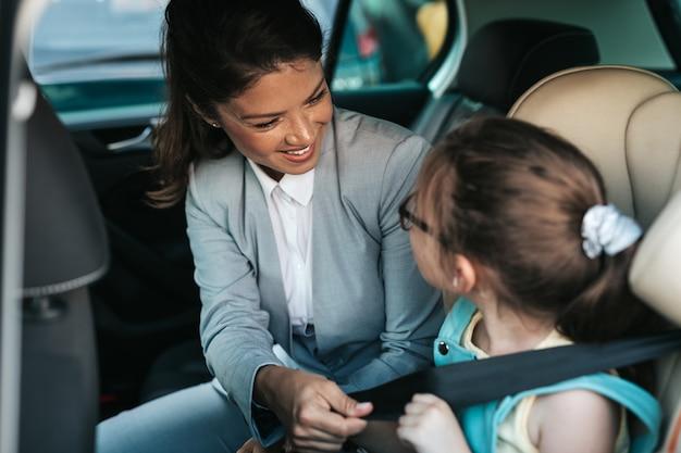 Giovane imprenditrice che aiuta sua figlia ad allacciare le cinture di sicurezza in macchina mentre la ragazza è seduta su un seggiolino per auto di sicurezza.