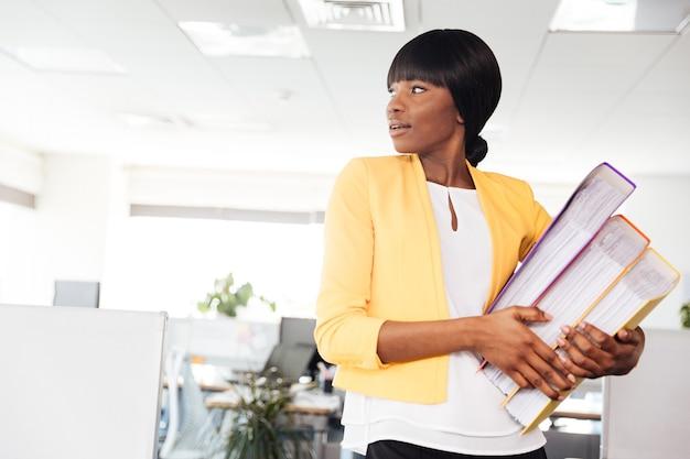 Giovane imprenditrice in possesso di cartelle e distoglie lo sguardo in ufficio