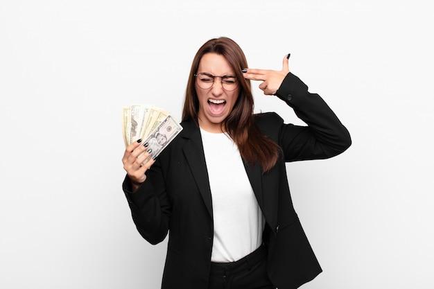 Giovane imprenditrice in possesso di denaro e facendo segno di pistola con la mano che punta alla testa