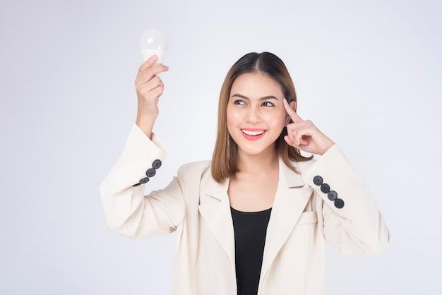 Una giovane donna d'affari tiene in mano la lampadina che indossa un abito su sfondo bianco studio