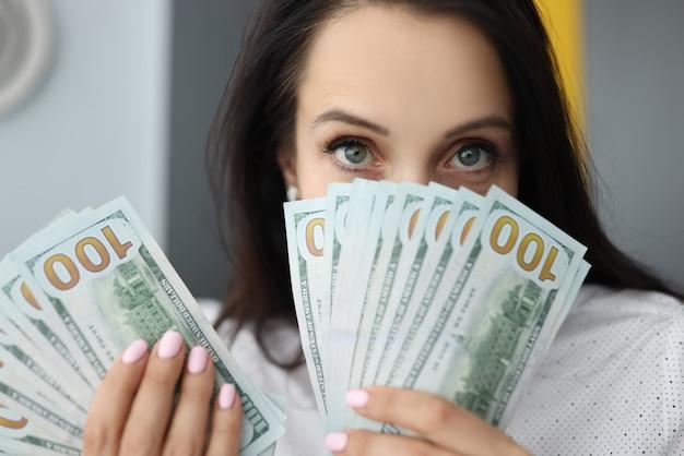 La giovane donna di affari sta tenendo molti dollari americani nelle sue mani, coprendosi il fronte. esborso del concetto di garanzie sociali di prestiti.