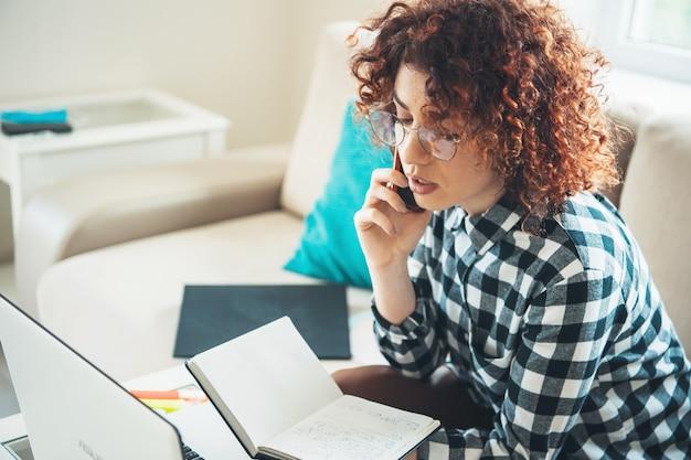 La giovane donna d'affari sta parlando al telefono mentre lavora con alcune cartelle e documenti sul laptop