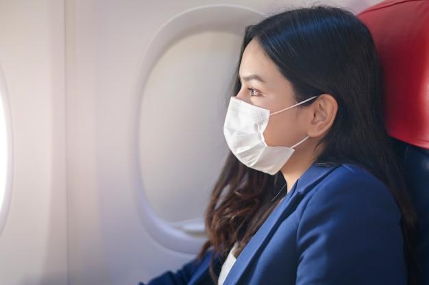 Una giovane imprenditrice indossa una maschera protettiva a bordo dell'aereo, viaggia sotto pandemia covid-19, viaggi di sicurezza, protocollo di allontanamento sociale