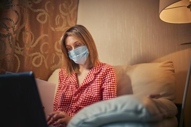 Giovane imprenditrice in una maschera protettiva medica lavora da casa