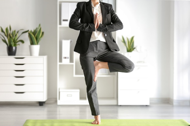 Giovane imprenditrice a praticare yoga in ufficio