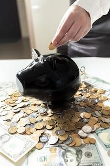 Giovane donna di affari che mette moneta nel salvadanaio nero black