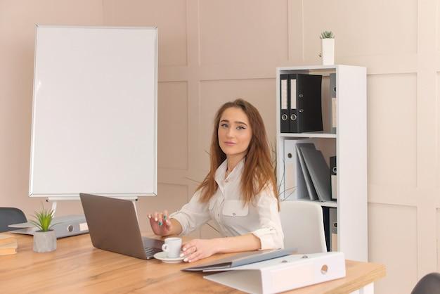 Giovane donna di affari che si siede al suo posto di lavoro mentre fa un rapporto di affari, calcola i dati annuali, legge i documenti e utilizza le tecnologie moderne