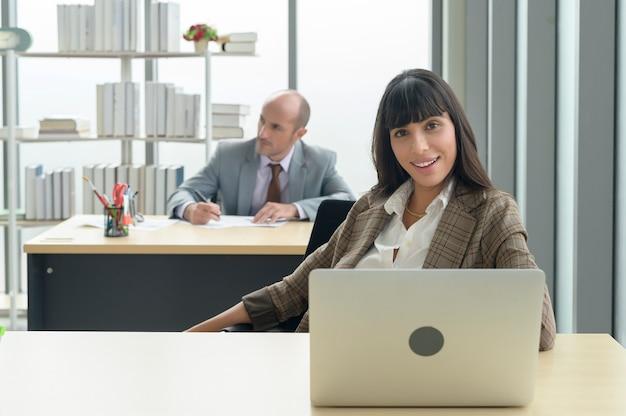 Una giovane donna d'affari seduta e lavora con il laptop in un ufficio moderno con un collega dietro