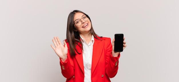 Giovane donna d'affari che sorride allegramente e allegramente, agitando la mano, accogliendoti e salutandoti, o salutandoti