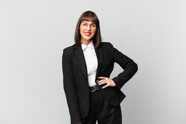 Giovane donna d'affari che sorride felicemente con una mano sull'anca e un atteggiamento fiducioso, positivo, orgoglioso e amichevole