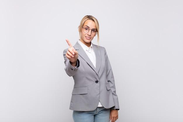 Giovane donna di affari che sorride con orgoglio e sicurezza facendo posa trionfante al numero uno, sentendosi come un leader