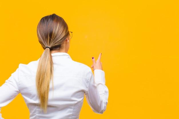 Giovane donna di affari che sta e che indica l'oggetto sullo spazio della copia, retrovisione sopra la parete arancio