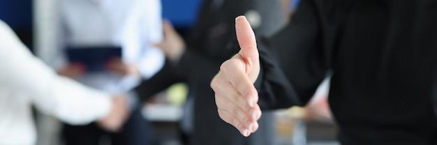 Giovane donna d'affari che allunga la mano per la stretta di mano sullo sfondo del primo piano dei colleghi