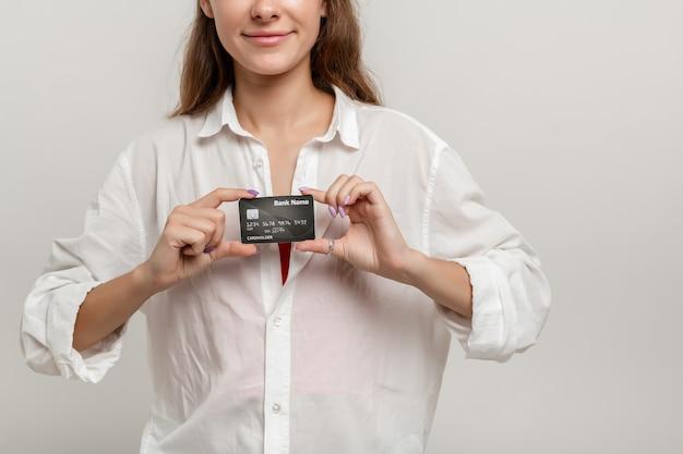 Giovane studentessa imprenditrice con in mano un biglietto da visita bianco e sorridendo alla telecamera da vicino