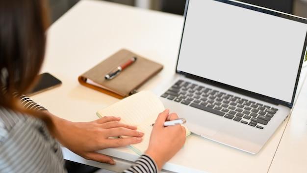 Giovane donna di affari che prende appunti nel modello dello schermo in bianco del computer portatile del computer portatile