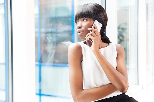 Giovane donna d'affari che parla al telefono e guarda nella finestra