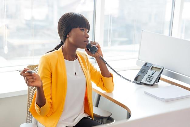 Giovane imprenditrice che parla al telefono in ufficio