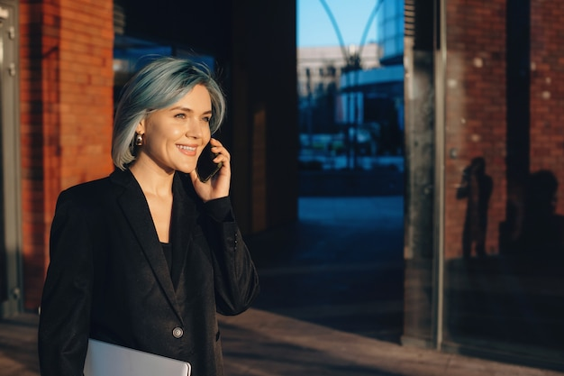 Giovane imprenditrice parlando al telefono e sorridere mentre si cammina con un computer