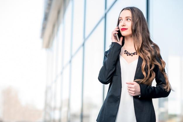 Giovane imprenditrice che parla con il telefono all'aperto vicino alla moderna facciata dell'edificio