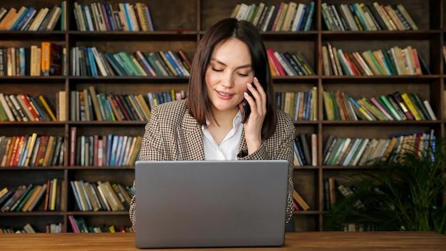 Giovane imprenditrice parla al telefono nero nella sala della biblioteca