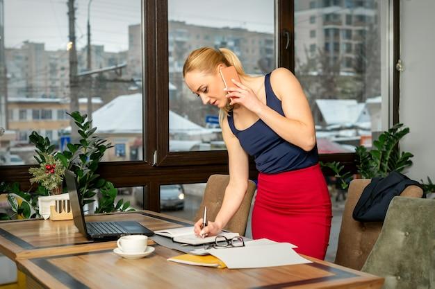 Giovane imprenditrice parla al telefono scrivendo note in piedi in ufficio o in un caffè