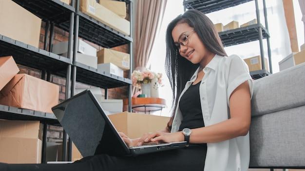 La giovane donna di affari che per mezzo del computer portatile lavora a casa