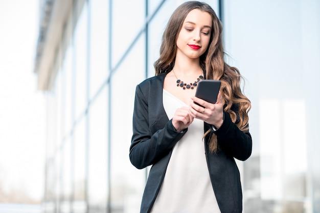 Giovane imprenditrice che utilizza il telefono all'aperto vicino alla facciata dell'edificio moderno