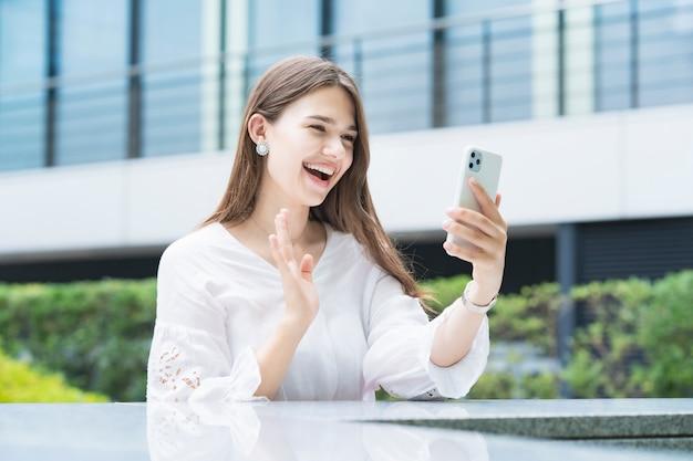 Giovane donna di affari che per mezzo di uno smartphone all'aperto