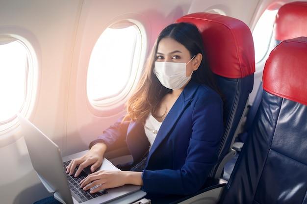 Una maschera facciale da portare della giovane donna di affari sta usando il laptop a bordo, nuovo viaggio normale dopo il concetto di pandemia covid-19