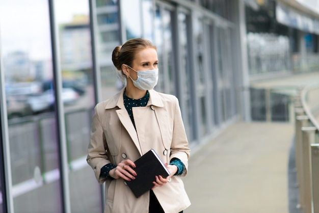 Una giovane imprenditrice che indossa una maschera di salute e parlando al telefono in città