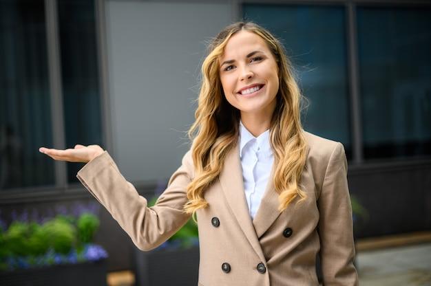Giovane imprenditrice vi dà il benvenuto in un ambiente urbano moderno
