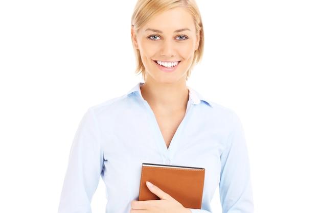 Una giovane donna d'affari con un'agenda su sfondo bianco