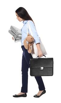 Giovane imprenditrice con valigetta, coniglietto giocattolo e cartelle camminando su sfondo bianco