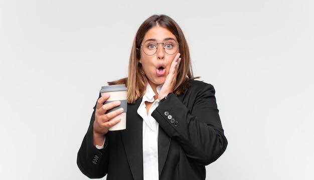 Giovane imprenditrice con una sensazione di caffè scioccata e spaventata