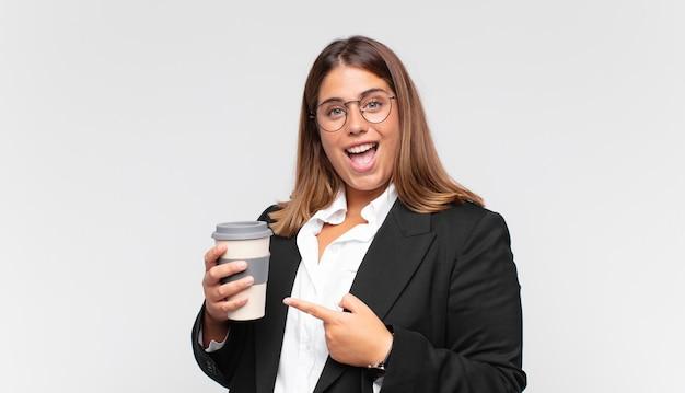Giovane imprenditrice con un caffè che sembra eccitato e sorpreso che punta di lato e verso l'alto per copiare lo spazio